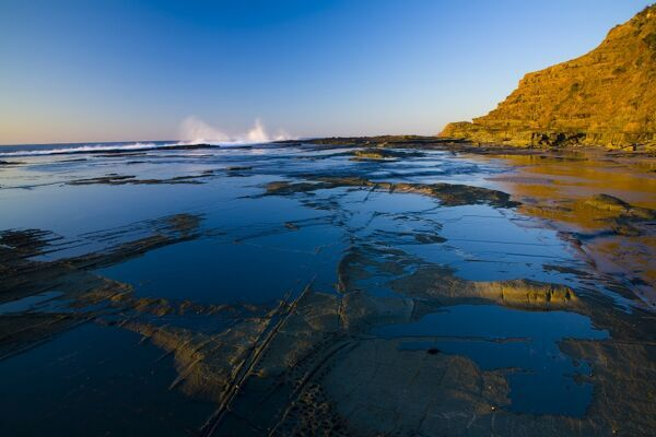 Australia, New South Wales, Royal National Park. Early morning light gently illuminates the picturesque coastline found at North Era, on the Royal National Park Coastal Track