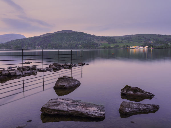 England, Cumbria, Lake District National Park. Shoreline of Low Wray at dusk refelcted in the still waters of Lake Windermere near the town of Ambleside