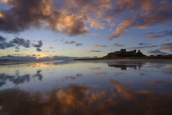 England, Northumberland, Bamburgh. The colours of dawn reflected on the wet, sandy beach at Bamburgh overlooked by Bamburgh Castle, located along the Northumberland Heritage Coast