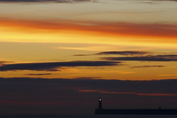 England, Tyne and Wear, Cullercoats. Sunrise looking towards the North Tyne Pier and lighthouse in Tynemouth