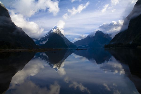 New Zealand, Southland, Fiordland National Park. A clearing storm above Mitre peak, reflected in the still waters of the Milford Sound