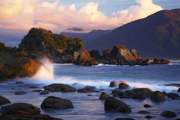 New Zealand, Southland, Fiordland National Park, The setting sun casts a golden glow over the boulders and coastline of Martins Bay, at the end of the Hollyford Track