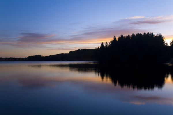 Scotland, Scottish Borders, Alemore Loch. Sunrise reflected in the tranquil waters of the Alemoor Loch, a popular place for recreational fishing near the town of Hawick