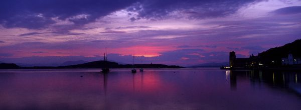 SCOTLAND, Scottish Highlands, Oban. The pinks and reds of a west coast sunset, looking towards the western isles and northern Oban