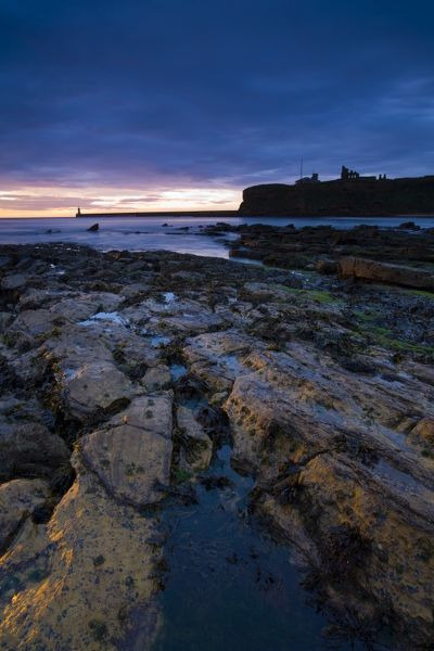 Sunrise over King Edward's Bay viewed from near Sharpness Point. The remains of Tynemouth Priory can be seen to