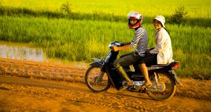 Girls riding along a dirt road in Cambodia.