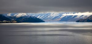 New Zealand, Otago, Lake Hawea. The Southern Alps revealed through a small gap between