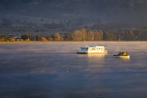 New Zealand, Otago, Lake Wanaka. The warm hues of sunset highlight the rising mist