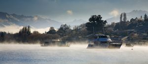 New Zealand, Otago, Lake Wanaka. Boats moored on Lake Wanaka engulfed by rising mist